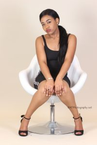 Coumba wearing a caual fit black dress